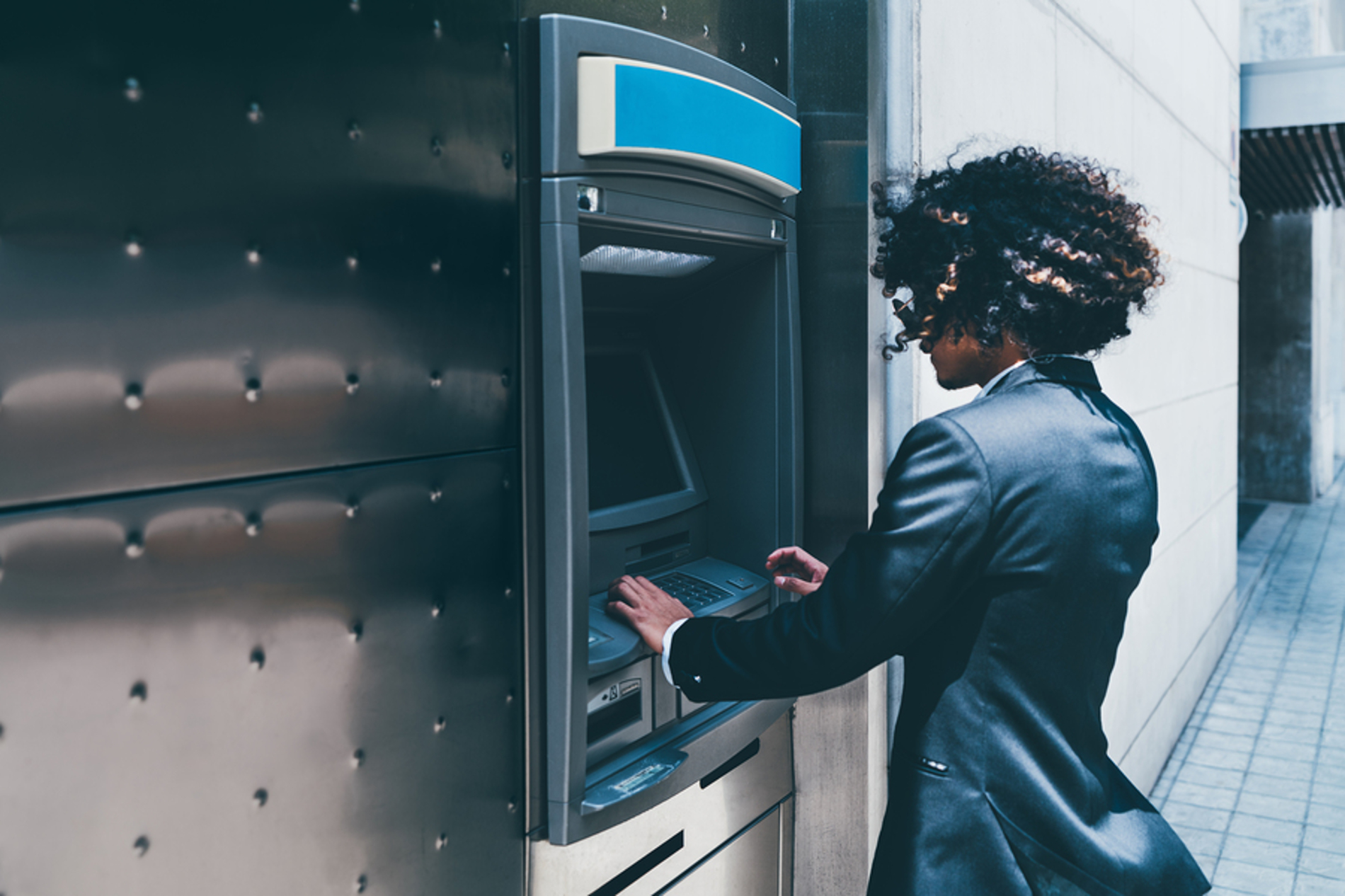 Woman operating an ATM.