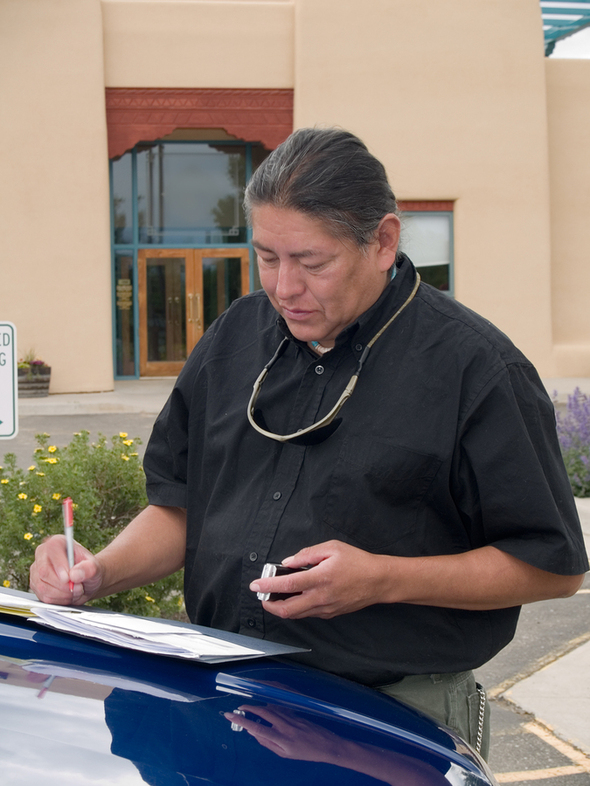 Native American gentleman writing in a folder near a car