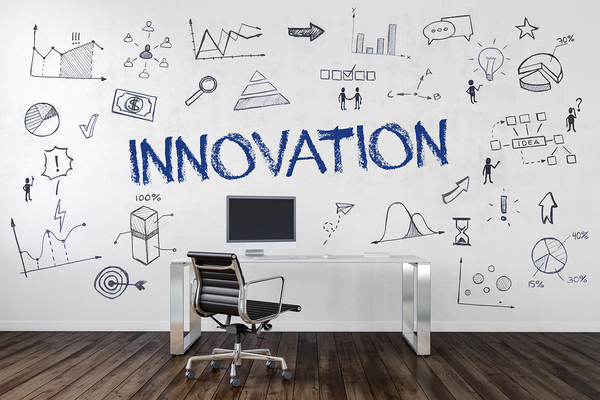 The word innovation written on a wall along with illustrations of people, charts and graphs.