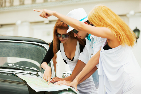 Group of three people looking at paper map on a car hood.