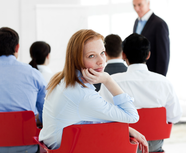 Woman in a conference appearing bored.
