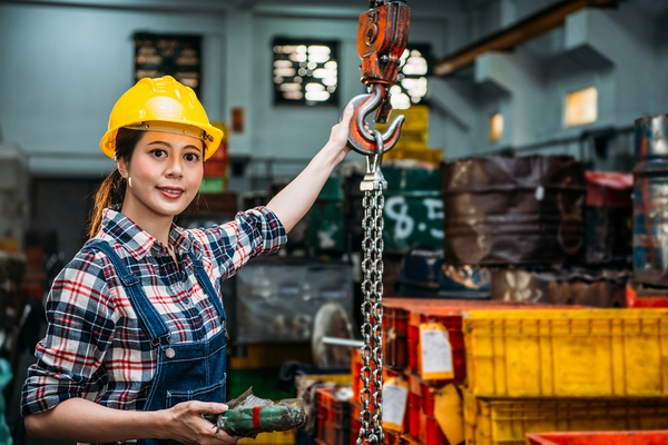 Woman with yellow hardhat working.