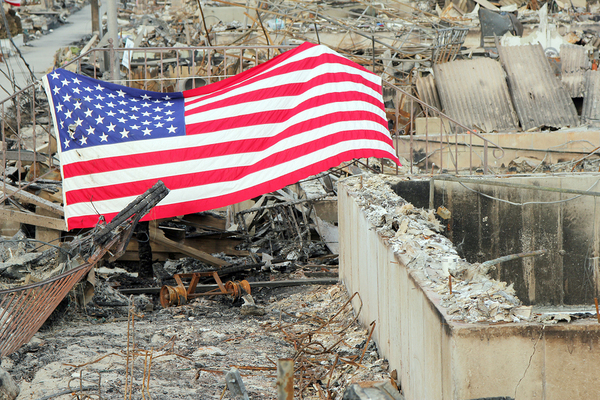 American flag across a destroyed building foundation.
