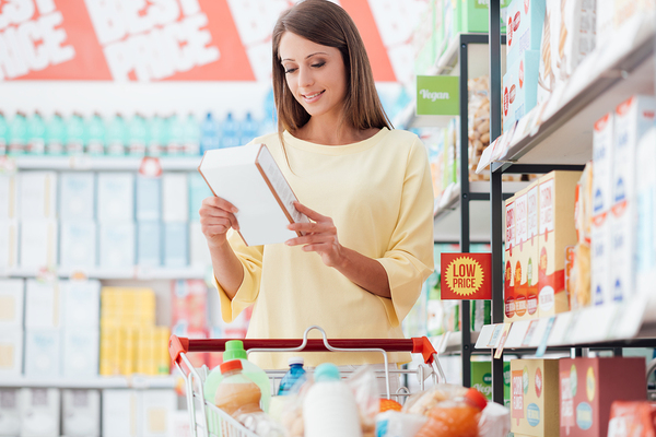 Woman reading a food label while shopping in a grocery store.