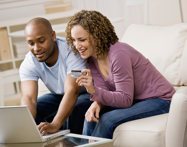 Couple sitting on a couple with a credit card making a purchase online.