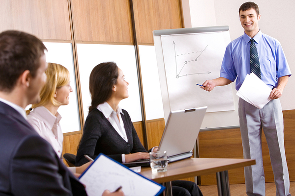 Man presenting information to a group of colleagues.