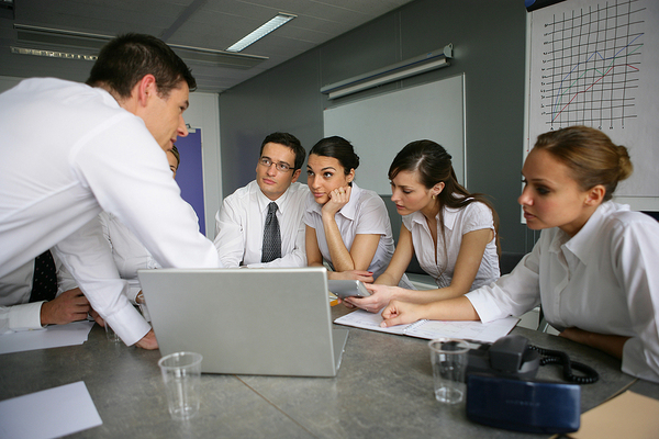Group of colleagues discussing information on a laptop computer.