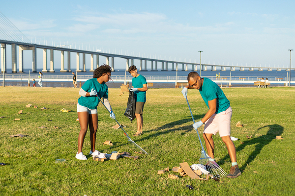 Group of people cleaning up debris from a park.