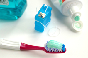 Toothbrush with toothpaste and floss.