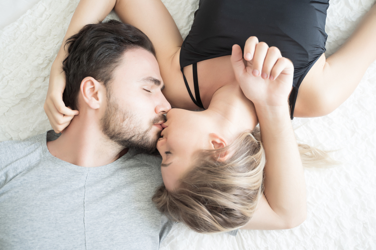 Young adult couple lying down kissing.