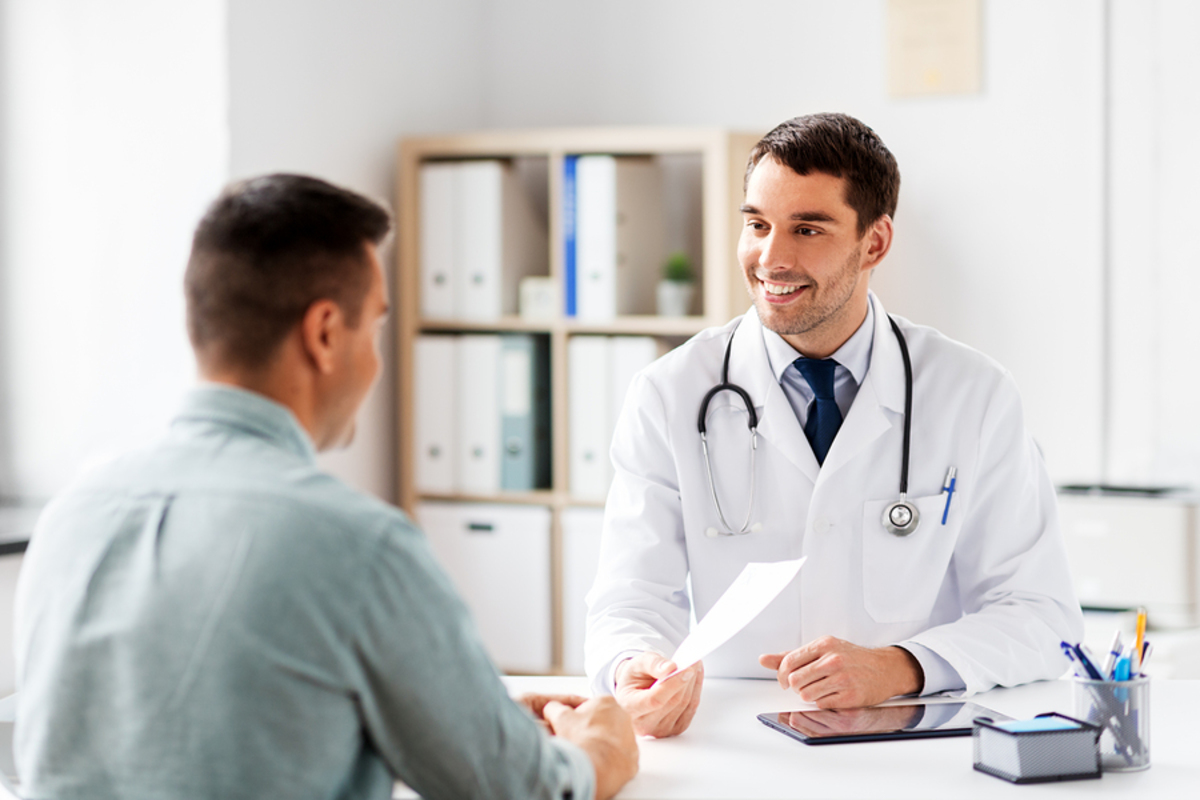 Medical doctor handing a prescription to a male patient.