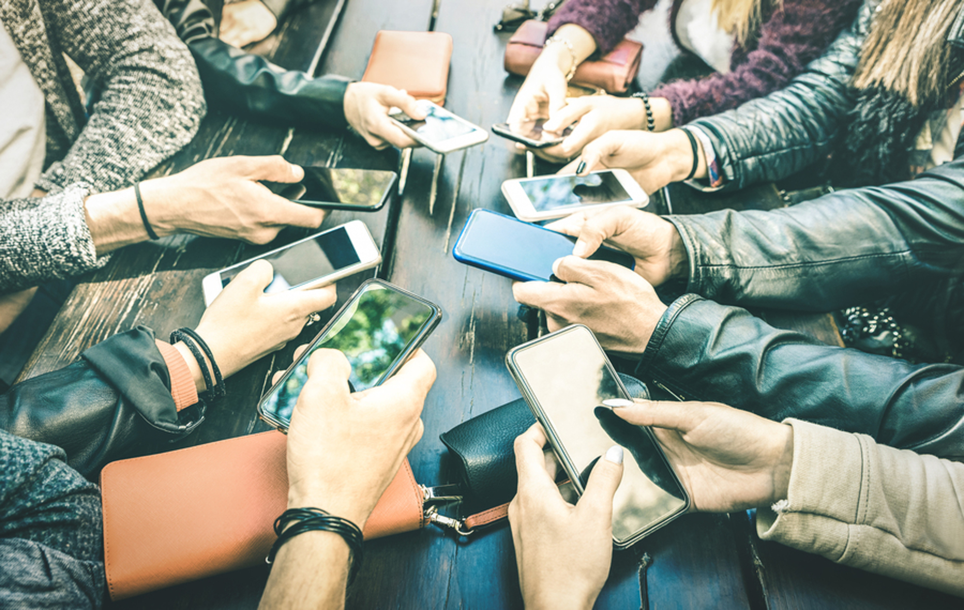 Group of people sitting around a table using their phones.