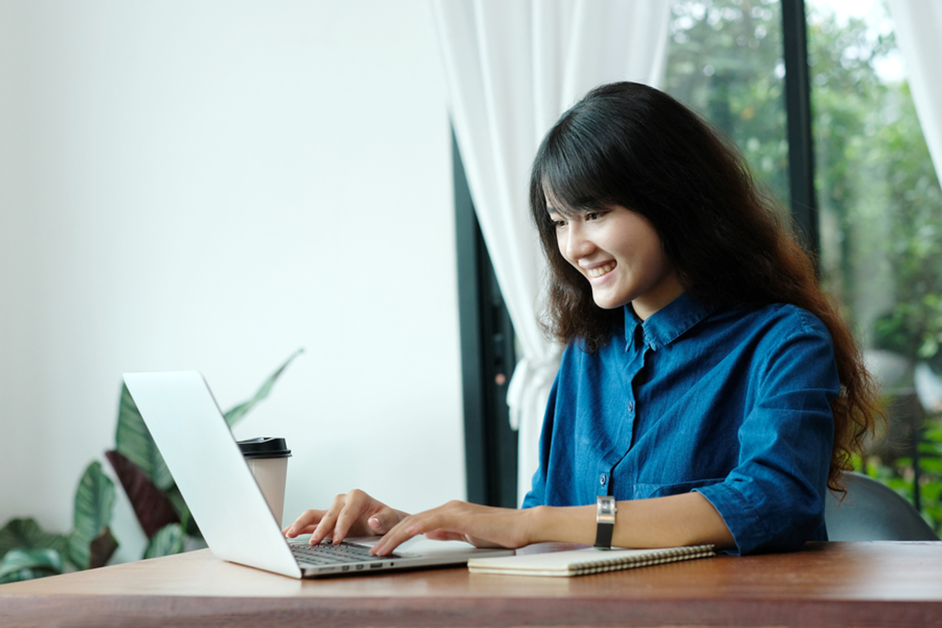 Happy woman typing on a laptop computer.