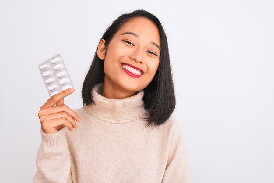 Smiling woman holding a pill packet.