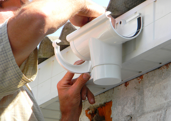 Person installing a downspout.