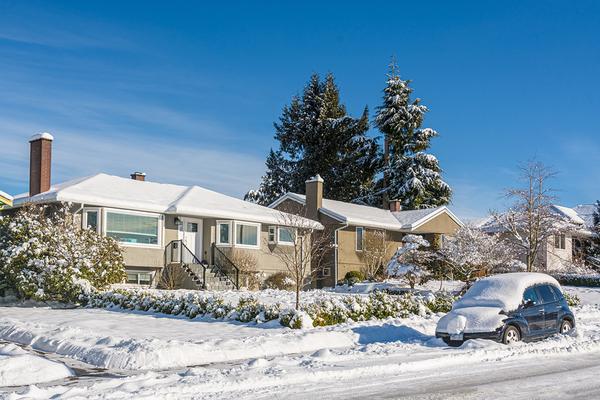 Neighborhood homes covered in snow.