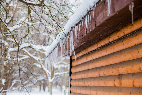 Icicles hanging off gutters located on the side of a house.