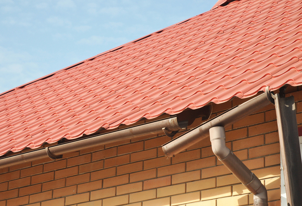 Red slate roof on a building with gutters and downspout.