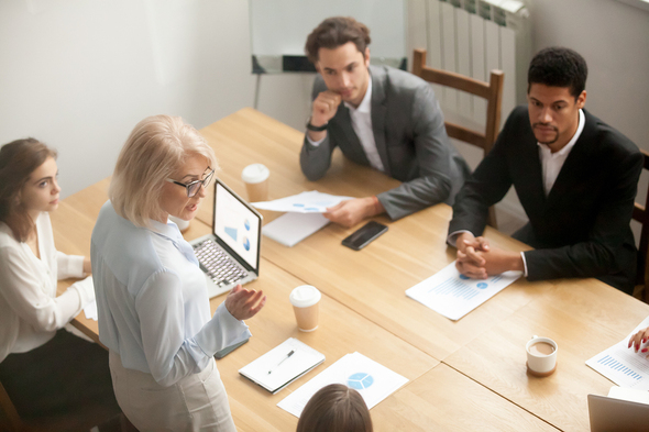 Group of people working around a conference table.