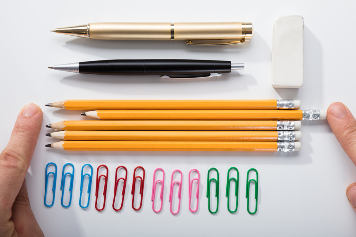 Table top with pencils, pens, eraser and paper clips.