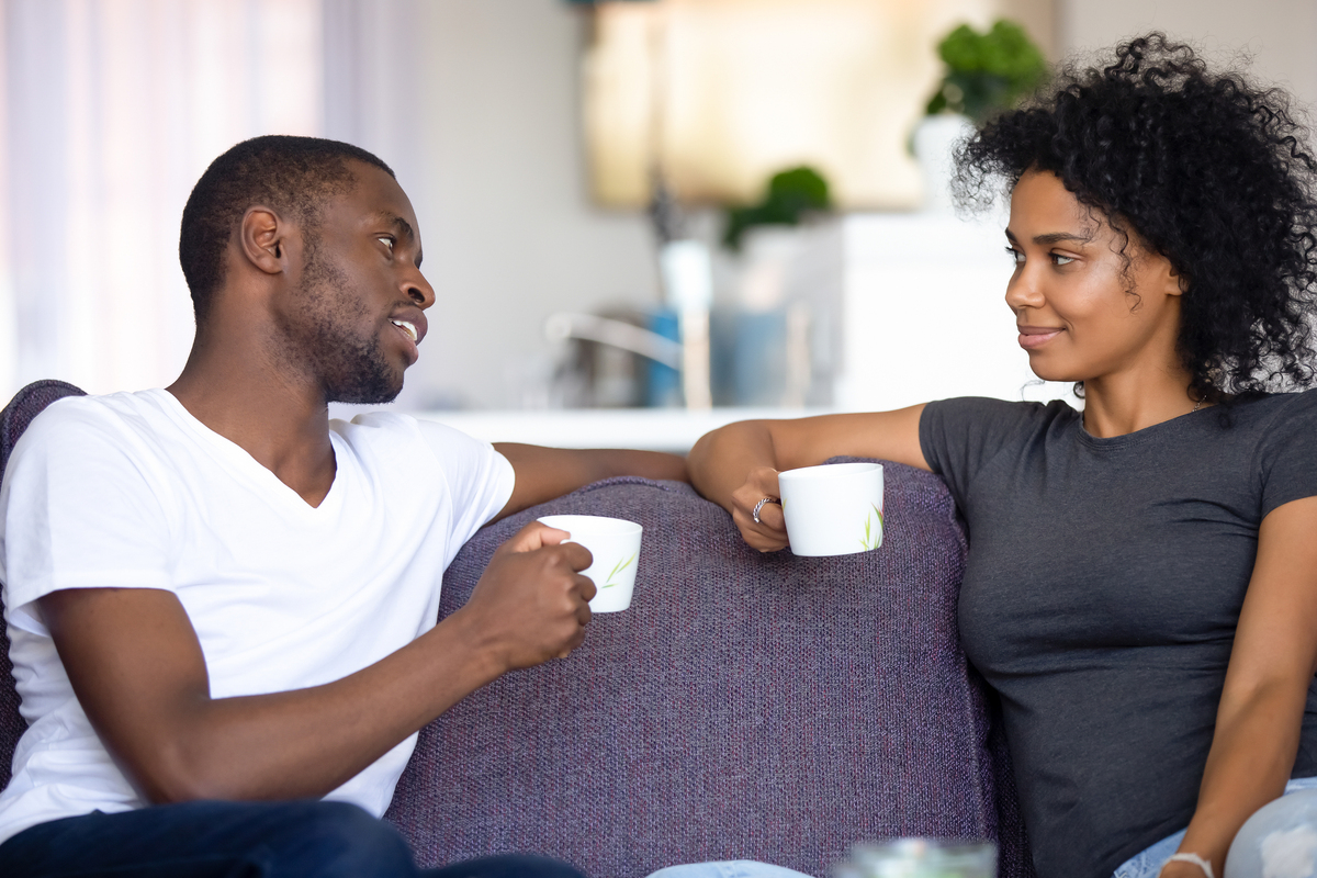 Happy couple sitting on a couch drinking coffee and having a discussion.