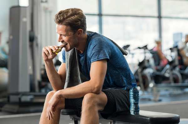 Man sitting on a bench at a gym eating an energy bar.