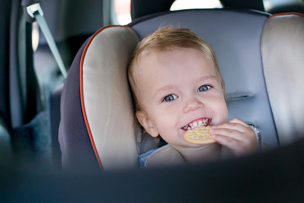 Child in a car seat eating a cracker.