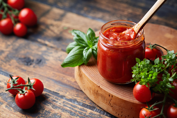 Glass jar of tomato sauce.
