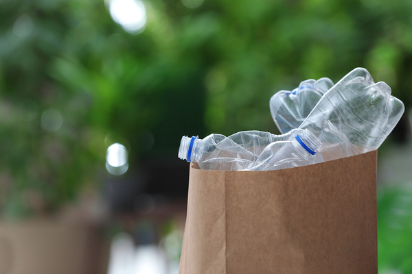 Paper bag filled with empty plastic bottles.