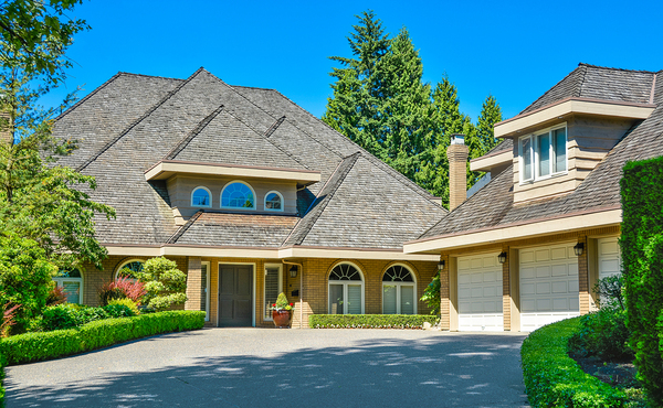Home with three car garage and shingled roof.