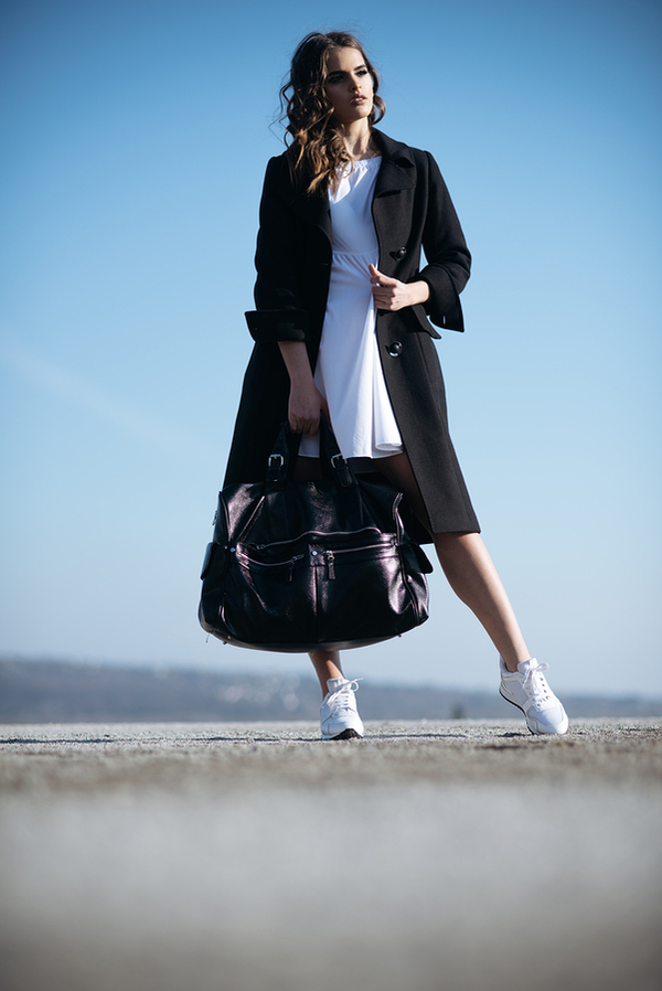 Woman modeling long coat and purse.