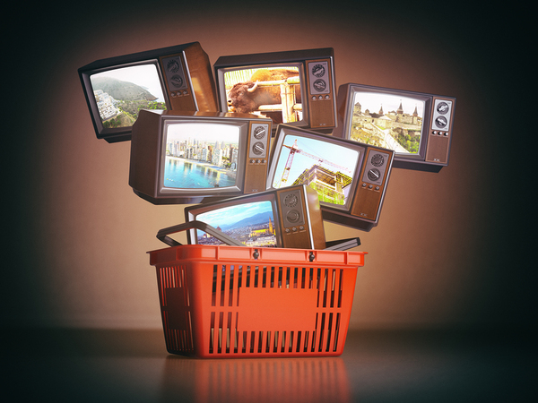 Multiple t.v.s in a shopping basket.
