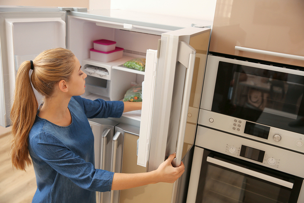 Woman placing food in a refrigerator.