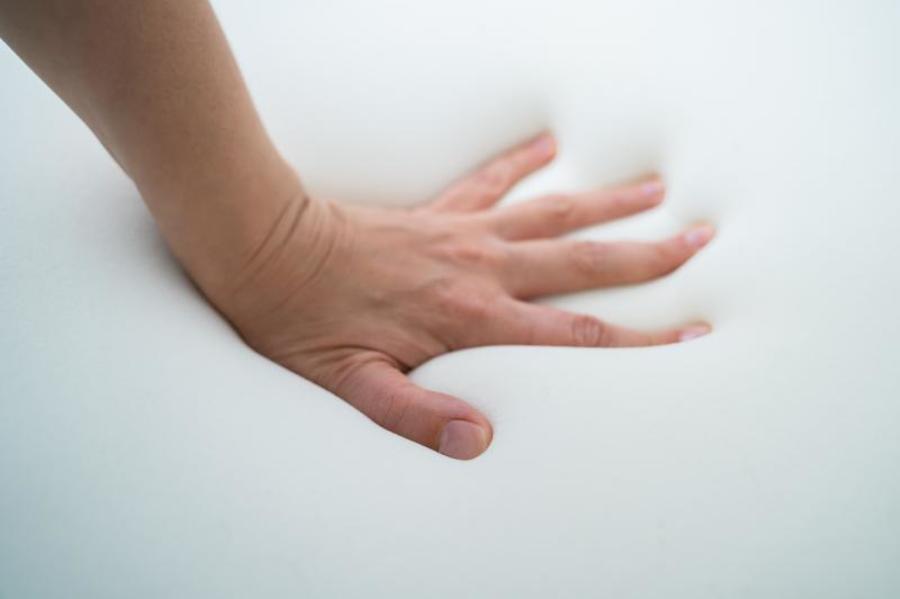 Pushing a hand into a foam cushion.