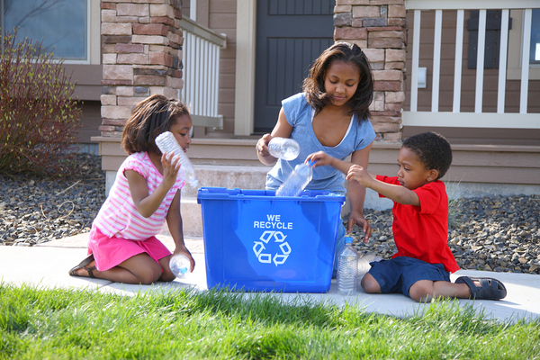 Family placing plastic bottles in a recycling bin.