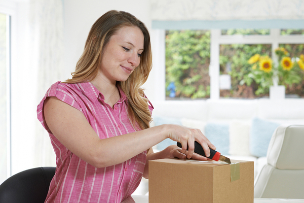 Woman opening a cardboard box.