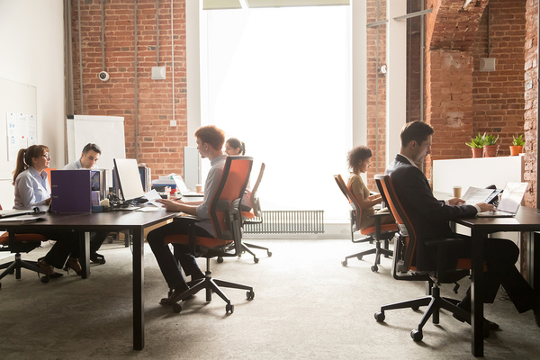 Group of people working together in an open office space.