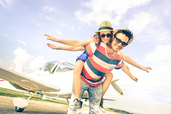 Young couple standing in front of a small airplane.