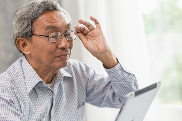 Older gentleman about to take off his glasses while looking at a tablet.