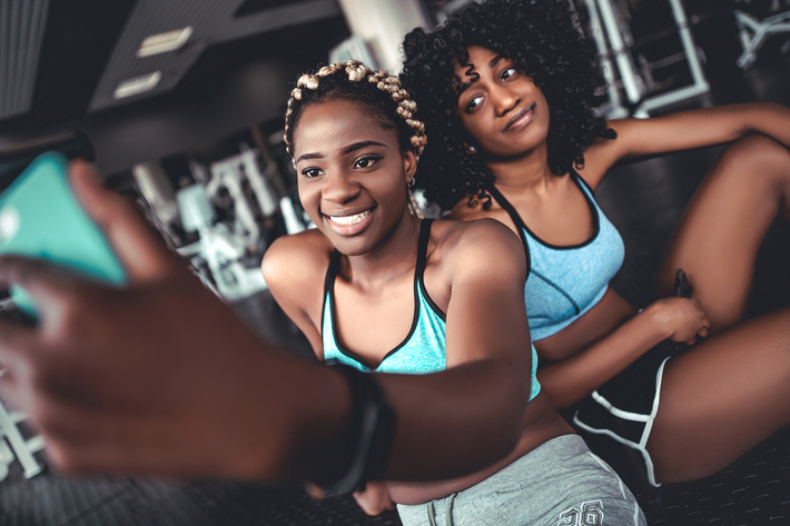 Two women taking a photo together in a gym.