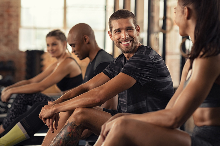 Group of people sitting on exercise rowing machines.
