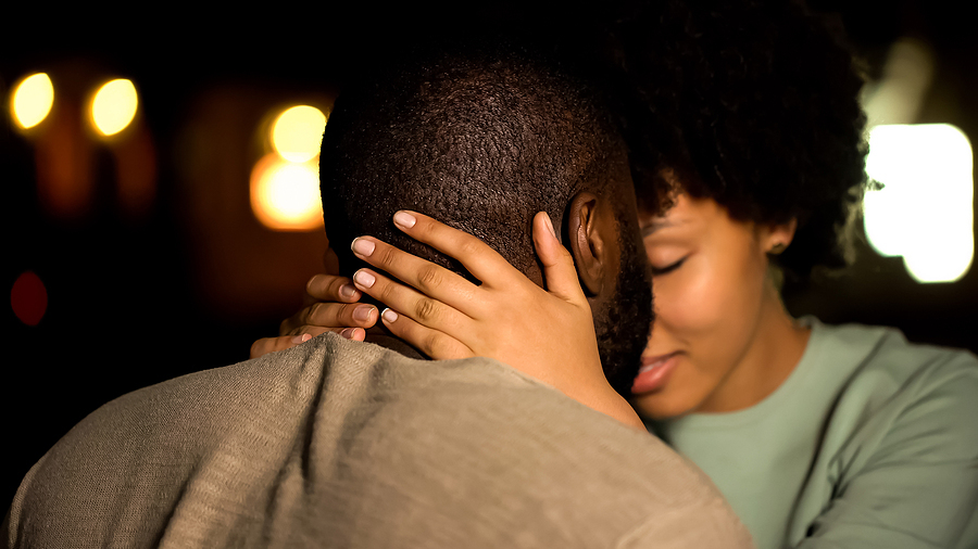 Couple touching foreheads in an embrace.