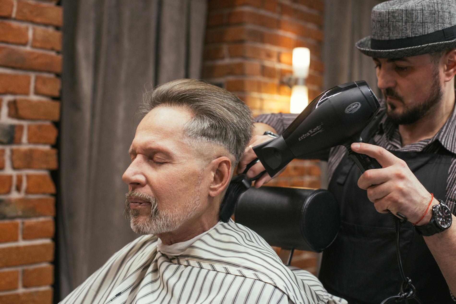 Man getting his hair cut at a barbers.