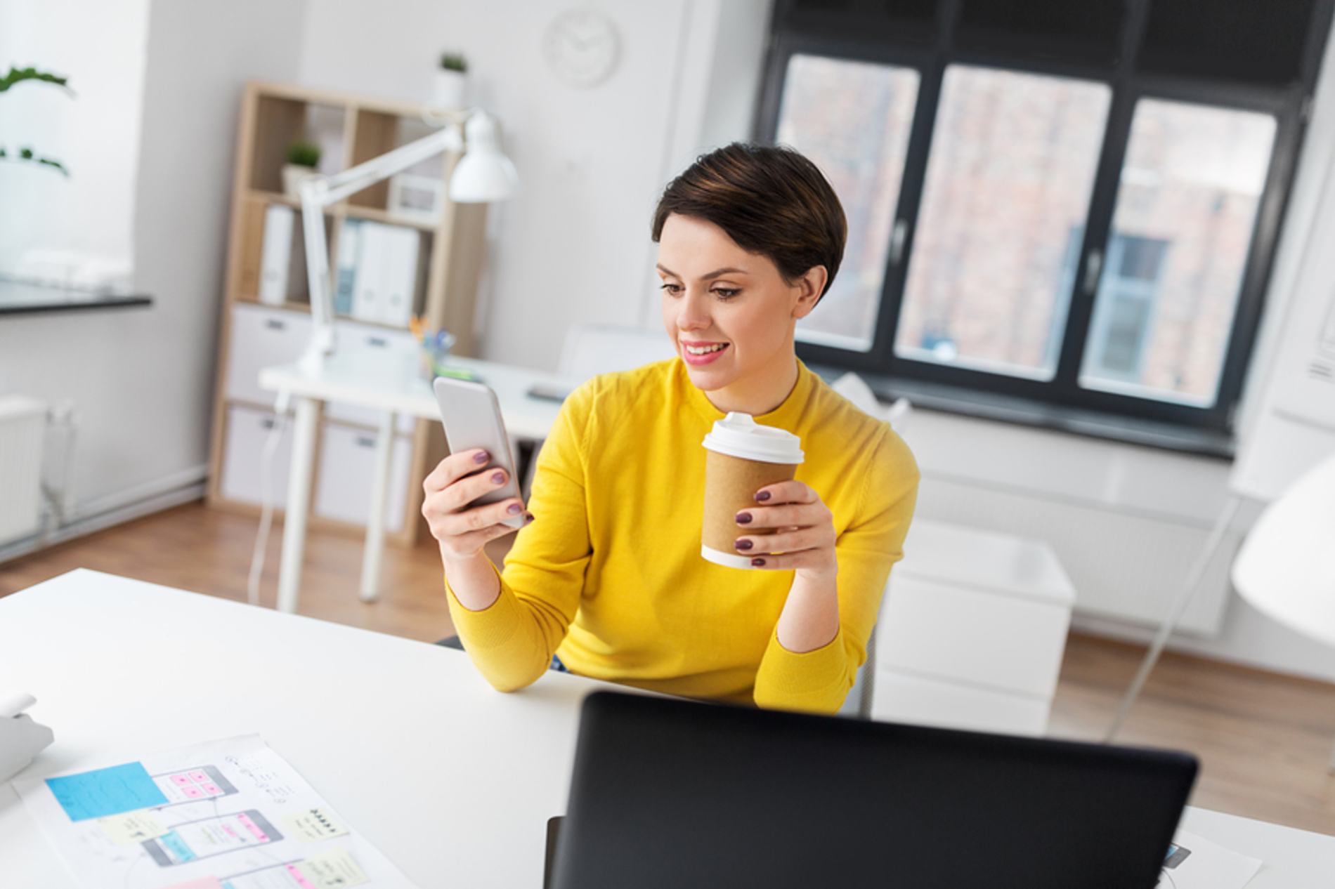 Young woman sitting at her desk looking at her phone and drinking a cup of coffee.