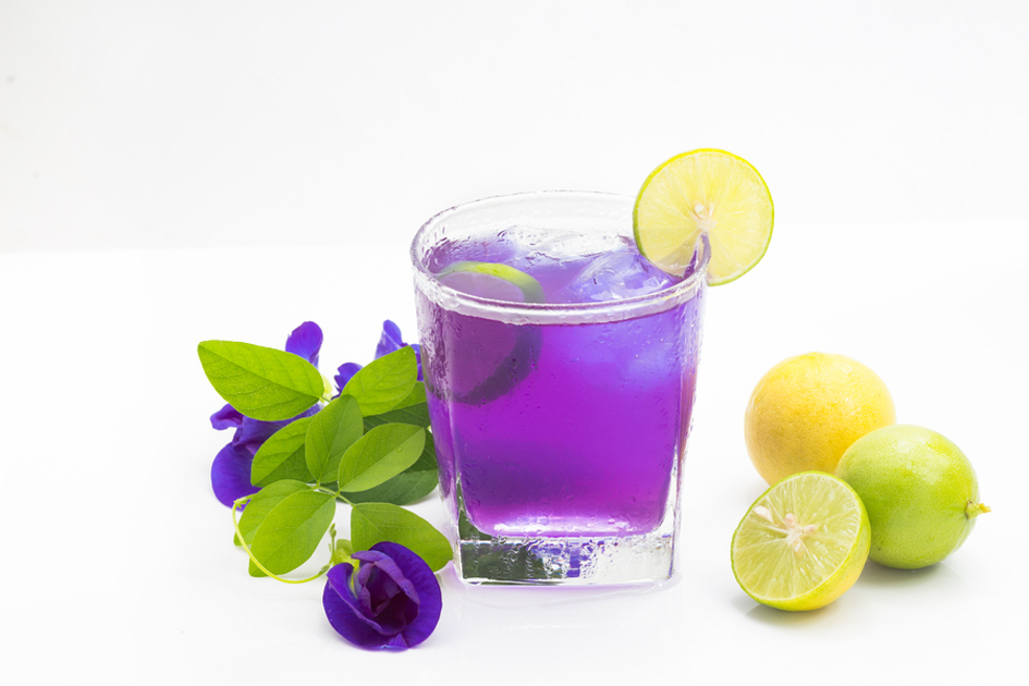 Purple botanical beverage with limes and lemons.