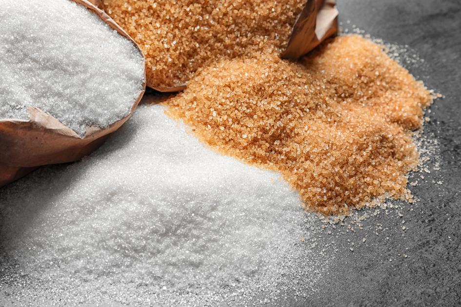 Sugar and brown sugar on a tabletop.