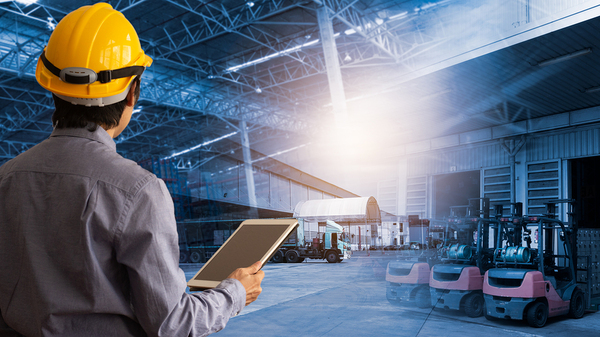Man with a hardhat holding a tablet.