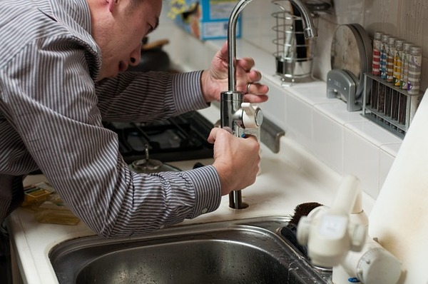 Plumber repairing a faucet on a sink.