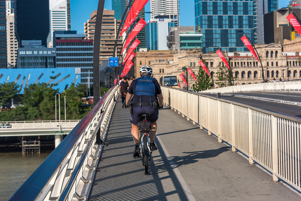 Person riding a bike over a bridge.