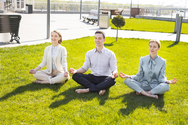 Three people sitting on the grass with legs crossed relaxing.